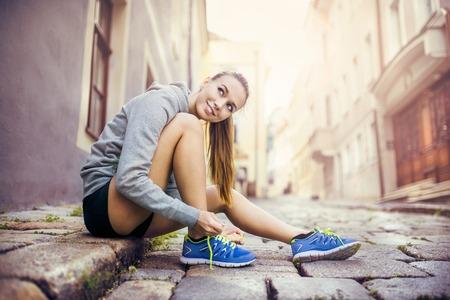 Corredor de sexo femenino joven está atando sus zapatos para correr en el pavimento de baldosas en el centro antiguo de la ciudad Foto de archivo - 33161014