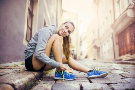 Young female runner is tying her running shoes on tiled pavement in old city center