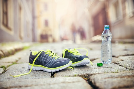 water shoes: Running shoes and bottle of water left on tiled pavement in old city center Stock Photo