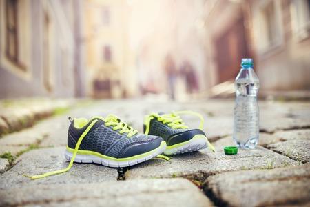 Zapatos corrientes y botella de agua que queda en el pavimento de baldosas en el centro antiguo de la ciudad Foto de archivo - 33161015