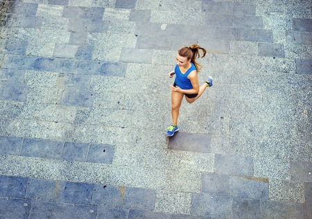 High angle view of young female runner jogging on tiled pavement old city on center.