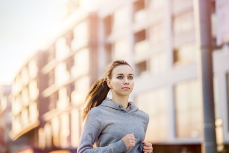 Young female runner in hoody is jogging in the city\ street