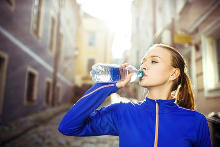 Young female runner is having break, drinking water during the run in city center photo