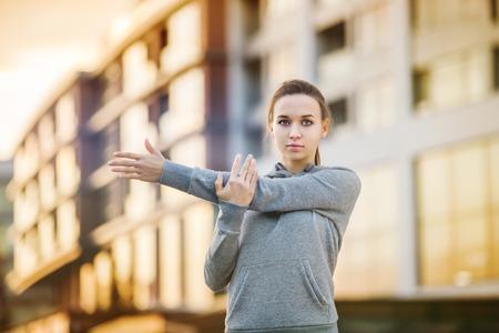 フーディの若い女性ランナーが街の通りに実行する前にストレッチします。