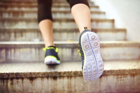 escalera: Corredor femenino subir corriendo las escaleras en el centro de la ciudad, primer plano en los zapatos