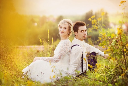 mariage: Young wedding couple enjoying romantic moments sitting on a meadow, summer nature outdoor