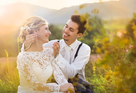 Young wedding couple enjoying romantic moments sitting on a meadow, summer nature outdoor photo