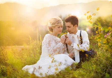 Jonge bruidspaar geniet romantische momenten zittend op een weide, zomer nave openlucht Stockfoto