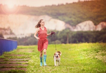 wellies: Young woman in dress and blue wellies walk her beagle dog in green nature