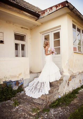 Beautiful young blonde bride with veil posing by old house photo