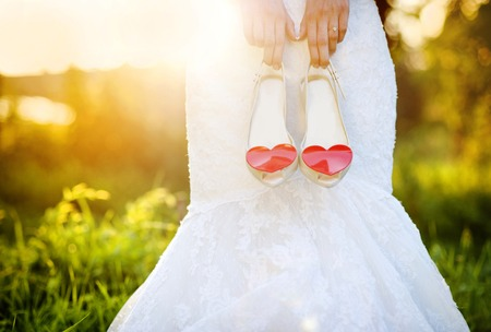red shoes: Photograph of a unrecognizable bride holding wedding shoes with red hearts Stock Photo