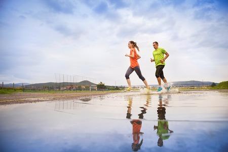 healthy lifestyle: Pareja joven que se ejecuta en el asfalto en salpicaduras tiempo lluvioso en los charcos. Foto de archivo