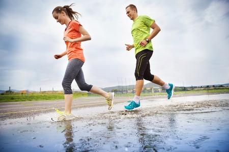 uomo sotto la pioggia: Giovane coppia in esecuzione su asfalto in tempo piovoso schizzi nelle pozzanghere.