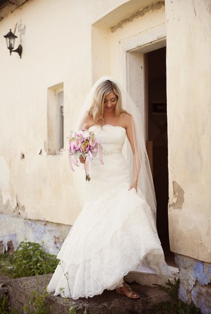 Beautiful young blonde bride posing by old house photo