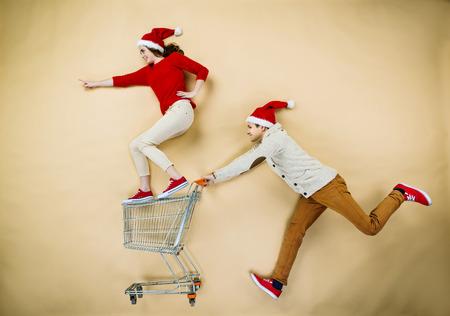 Jong paar in kerst hoeden met plezier lopen met het winkelen karretje tegen de beige achtergrond