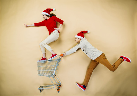 Young couple in Christmas hats having fun running with shopping trolley against the beige background Foto de archivo