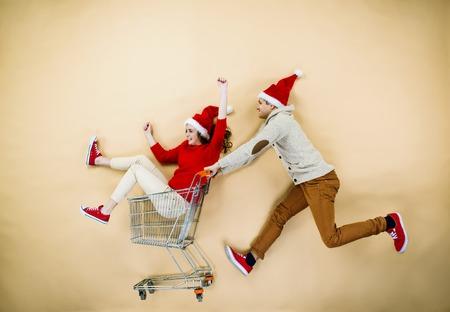 gente loca: Joven pareja en sombreros de la Navidad que se divierten corriendo con carrito de la compra contra el fondo beige Foto de archivo