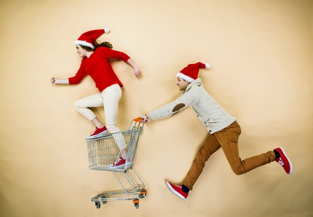 Young couple in Christmas hats having fun running with shopping trolley against the beige background photo