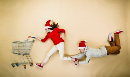 couple having fun: Young couple in Christmas hats having fun running with shopping trolley against the beige background Stock Photo