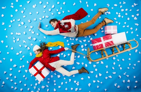 christmas sleigh: Happy young couple on sledge with Christmas presents against the blue background with snowflakes