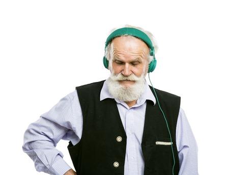 la escucha activa: Hombre barbudo activo mayor con los auriculares escuchando música aislado en fondo blanco