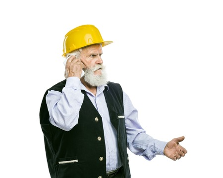 Senior manual worker with yellow helmet calling on the phone isolated over white background photo