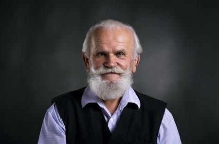 hombre con barba: Retrato de hombre con barba de edad, posando en estudio sobre fondo negro