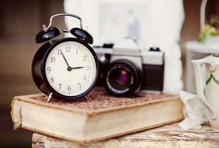 Group of objects on vintage wooden table. old alarm clock, retro camera, book photo