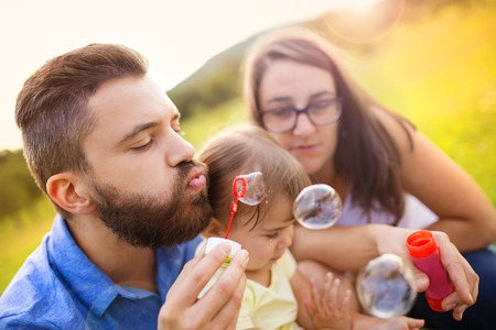 Happy little girl with her parents blowing bubbles in summer nature photo