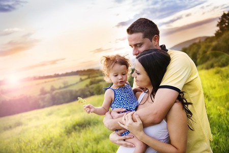 Happy pregnant family with little daughter spending time together in summer nature photo