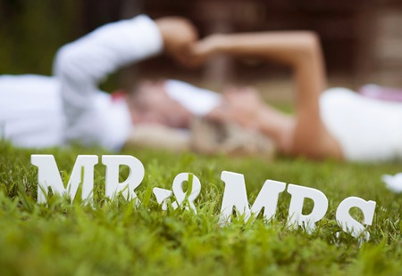 Happy bride and groom enjoying their wedding day in green nature, lying on grass 写真素材