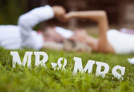 Gelukkige bruid en bruidegom genieten van hun trouwdag in de groene natuur, liggend op het gras Stockfoto - 33393199