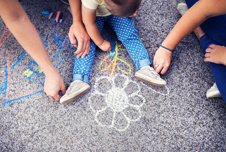 어린 소녀의 폐쇄와 그녀의 부모는 보도에 크레용으로 그리기