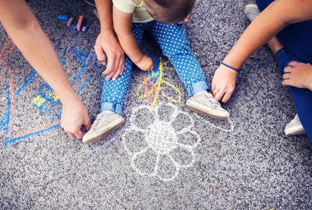 Close-up van meisje en haar ouders tekenen met krijt op de stoep