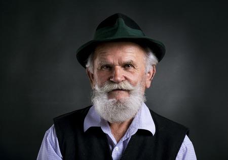 Portret van de oude bebaar Beierse mens in traditionele vilten hoed, die in studio op zwarte achtergrond stellen