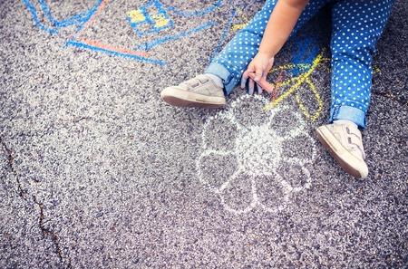 niños dibujando: Close up de la niña en los zapatos de lona de dibujo con tizas en la acera Foto de archivo