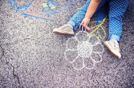 Close up of little girl in canvas shoes drawing with chalks on the sidewalk