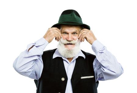 Portret van de oude gebaarde Beierse mens in traditionele vilten hoed, die in studio op witte achtergrond stellen