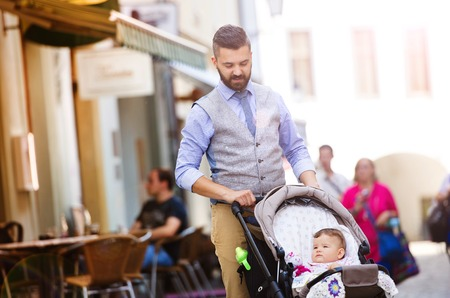 Handsome hipster modern businessman with beard walking with baby in pram in town photo