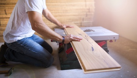 Unrecognizable handyman cutting plywood on circular saw in the new house photo