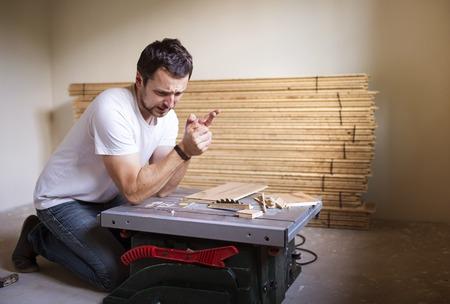 circular saw: Young handyman having accident during cutting plywood on circular saw