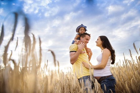 Happy pregnant family with little daughter spending time together in sunny field 版權商用圖片