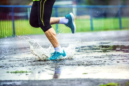 Young man running on asphalt sports field in rainy weather. Details of legs and sports shoes splashing in puddles. Stok Fotoğraf