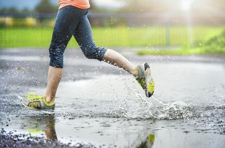 Jonge vrouw die op asfalt sportveld in regenachtig weer. Details van de benen en sportschoenen spetteren in plassen.