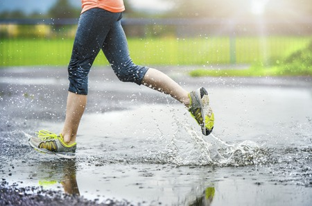 Young woman running on asphalt sports field in rainy weather. Details of legs and sports shoes splashing in puddles.