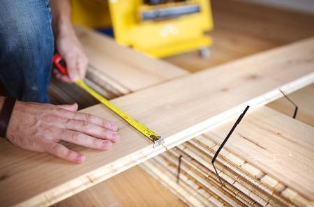 Close up of handymans hands measuring wood flooring photo