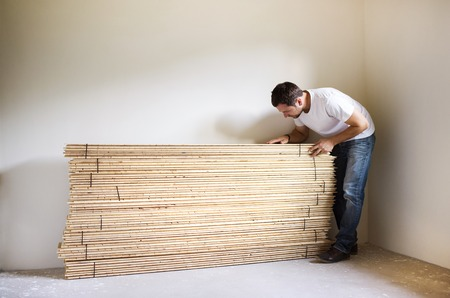 Young handyman installing wooden floor in new house photo