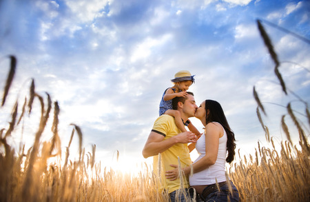 Happy pregnant family with little daughter spending time together in sunny field Stock Photo