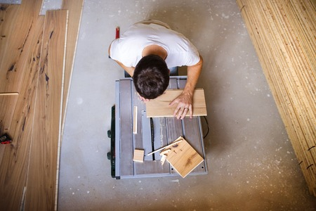 circular saw: High angle view of handyman cutting plywood on circular saw in the new house