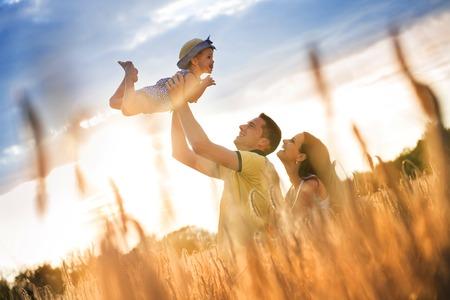 日当たりの良いフィールドで一緒に過ごす時間の小さな娘と幸せな妊娠している家族
